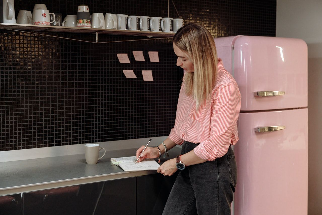 A woman writing down the measurements of her fridge