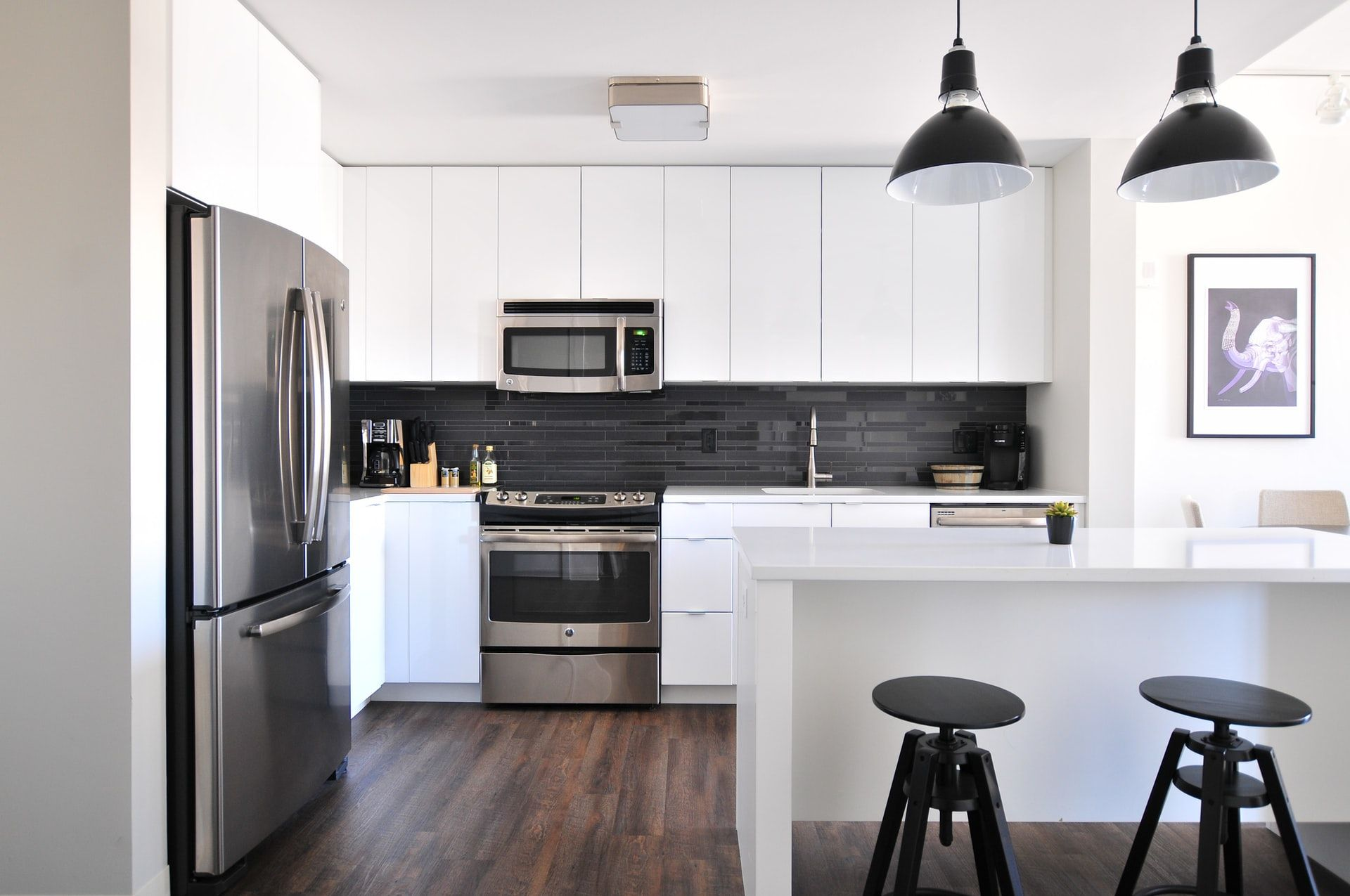 A kitchen interior with a big refrigerator and hardwood kitchen floors